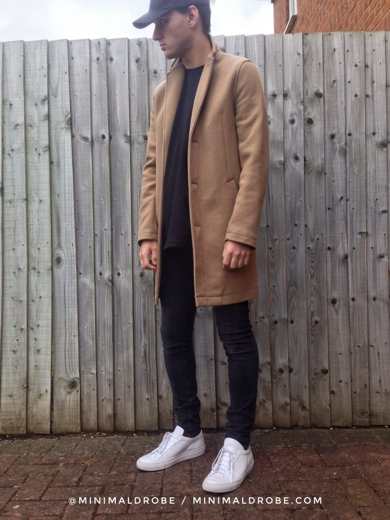 Camel overcoat with a black baseball cap, black t-shirt, black skinny jeans and white sneakers.